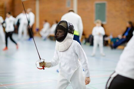 Little kid boy fencing on a fence competition. Child in white fencer uniform with mask and sabre. Active kid training with teacher and children. Healthy sports and leisure. Stockfoto