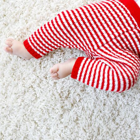 Close-up of baby body and legs in red Santa Clause trousers. New born child, little girl or boy. Kid having fun. Family, new life, childhood, holiday concept. Closeup for Christmas postcard. 版權商用圖片