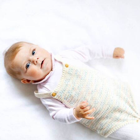 Portrait of cute baby girl wearing vintage clothes. New born child, little girl looking at the camera and crawling. Family, new life, childhood, beginning concept. Baby learning grab.