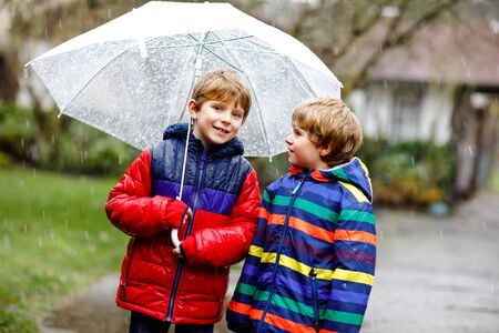 Two little kid boys on way to school walking during sleet, rain and snow with umbrella on cold day. Children, best friends and siblings in colorful fashion casual clothes Stockfoto - 133478530