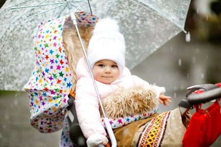 Cute little beautiful baby girl sitting in the pram or stroller on cold day with sleet, rain and snow. Happy smiling child in warm clothes, fashion stylish baby coat. Baby with big umbrella 写真素材