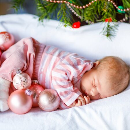 One week old newborn baby with pink balls near Christmas tree with colorful garland lights on background. Closeup of cute child, little baby girl sleeping. Family, Xmas, birth, new life Archivio Fotografico - 133151490