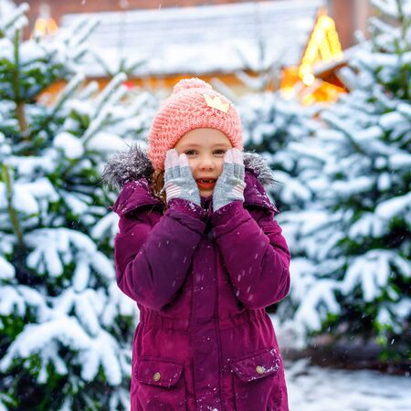 Cute little smiling kid girl on christmas tree market. Happy child in winter clothes choosing xmas tree on xmas market with lights on background on winter snow day.