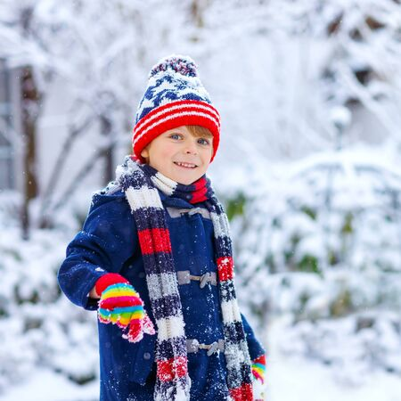 Preschool kid boy in colorful clothes playing outdoors during strong snowfall. Active leisure with children in winter on cold snowy days. Happy child having fun, playing with snow. Winter fashion.