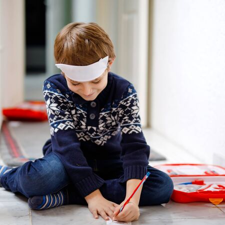 Adorable little school kid boy playing doctor with toy set. Happy healthy child having fun with role games and thinking about future job in hospital