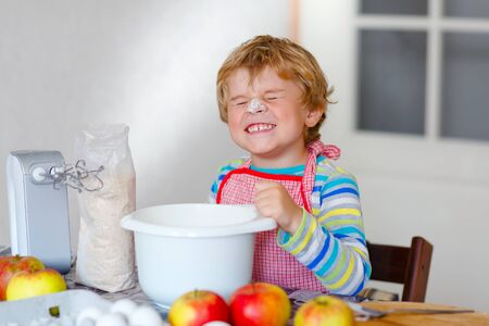Cute little happy blond preschool kid boy baking apple cake and muffins in domestic kitchen. Funny lovely healthy child having fun with working with mixer, flour, eggs, fruits. Little helper indoors 版權商用圖片