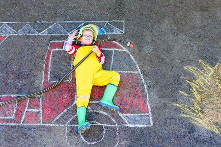 Ragazzino in uniforme da vigile del fuoco che si diverte con il disegno dell'immagine del camion dei pompieri con gesso colorato sull'asfalto. Da sopra. all'aperto. Bambino che sogna di spegnere il fuoco e la futura professione. Archivio Fotografico