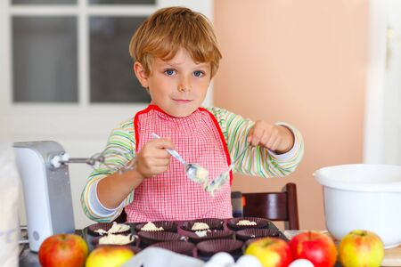 Cute little happy blond preschool kid boy baking apple cake and muffins in domestic kitchen. Funny lovely healthy child having fun with working with mixer, flour, eggs, fruits. Little helper indoors