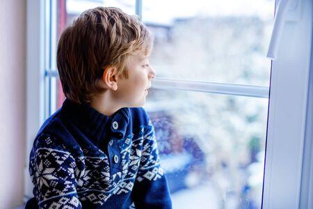 Happy adorable kid boy sitting near window and looking outside on snow on Christmas day or morning. Smiling healthy child fascinated observing snowfall and big snowflakes Standard-Bild - 134139385