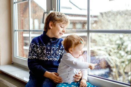Happy adorable kid boy and cute baby girl sitting near window and looking outside on snow on Christmas day or morning. Smiling children, siblings, little sister and brother looking on winter snowfall.