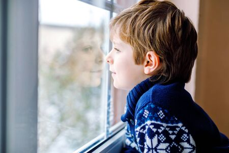 Happy adorable kid boy sitting near window and looking outside on snow on Christmas day or morning. Smiling healthy child fascinated observing snowfall and big snowflakes Standard-Bild - 134139387