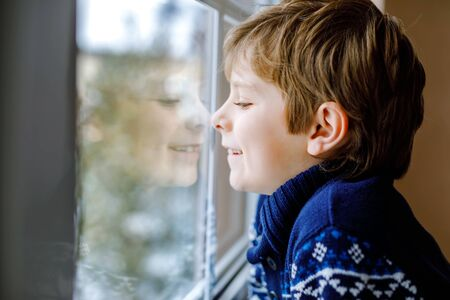 Happy adorable kid boy sitting near window and looking outside on snow on Christmas day or morning. Smiling healthy child fascinated observing snowfall and big snowflakes Standard-Bild - 134139388