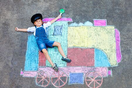 Happy little kid boy having fun with train or steam locomotive picture drawing with colorful chalks on ground. Children, lifestyle, concept. funny child playing and dreaming of future and profession