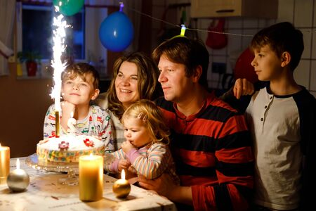 Adorable little toddler girl celebrating second birthday. Baby child, two kids boys brothers, mother and father together with cake and candles. Happy healthy family portrait with three children