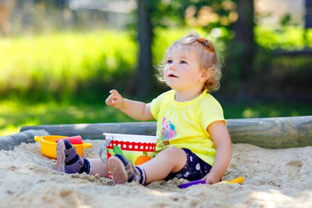 Cute toddler girl playing in sand on outdoor playground. Beautiful baby having fun on sunny warm summer sunny day. Happy healthy child with sand toys and in colorful fashion clothes. Stock Photo