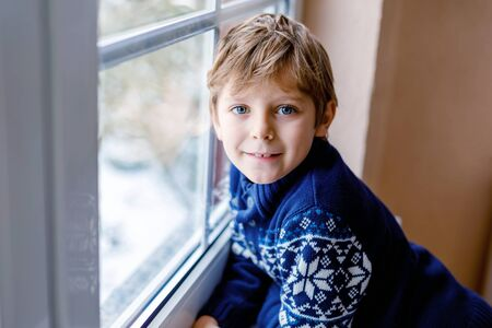 Happy adorable kid boy sitting near window and looking outside on snow on Christmas day or morning. Smiling healthy child fascinated observing snowfall and big snowflakes Standard-Bild - 134139522