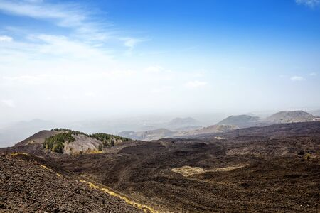 Panoramic wide view of the active volcano Etna on island Sicily, Italy extinct craters on the slope, traces of volcanic activity. Barren landscape of lava stones Stock Photo