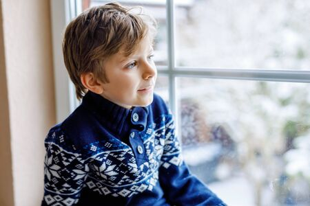 Happy adorable kid boy sitting near window and looking outside on snow on Christmas day or morning. Smiling healthy child fascinated observing snowfall and big snowflakes Standard-Bild - 134139558