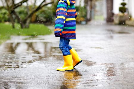 Close-up of kid wearing yellow rain boots and walking during sleet, rain and snow on cold day. Child in colorful fashion casual clothes jumping in a puddle. Having fun outdoors Standard-Bild - 134139575