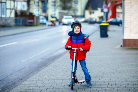 Gorgeous little school kid boy riding on scooter on way to elementary school. Child with safety helmet, school bag on rainy autumn or winter cold morning. Traffic in the city and schoolchildren Standard-Bild - 134139579