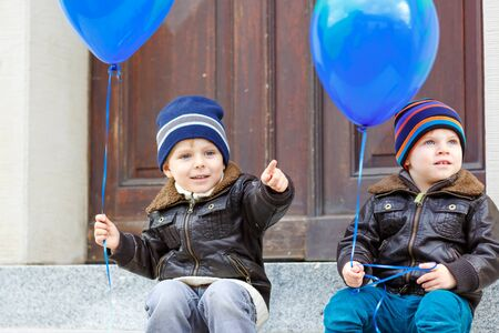 Two little kids boys playing with blue air balloons outdoors. Happy twins and toddler brothers smiling and laughing together. Healthy children outside on cold day in warm clothes.