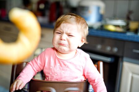 Cute little baby girl eating bread. Adorable child eating for the first time piece of pretzel or croissant. Healthy sad crying child. First teeth coming. At home indoors in the kitchen.