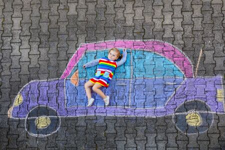 Adorable little toddler girl playing with colorful chalks and painting big car picture on asphalt. Happy baby child playing outside. Creative leisure for children outdoors in summer Banco de Imagens