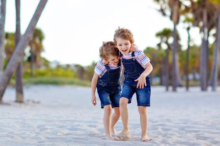Two little kids boys having fun on tropical beach, happy best friends playing, friendship concept. Siblings brothers, twins fighting, running and jumping in family look with palms trees on background. Stockfoto - 134194714