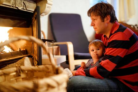 Middle age father sitting by fireplace with cute little baby girl at home. Happy family, dad with daughter make fire for Christmas time. Safe handling for kids