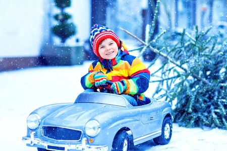 Beautiful little smiling kid boy driving toy car with Christmas tree. Happy child in winter fashion clothes bringing hewed xmas tree from snowy forest. Family, tradition, holiday. Stock fotó