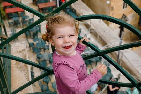 Portrait of beautiful little toddler girl in summer look clothes standing on balcony in Venice, Italy.