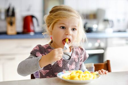Lovely toddler girl eating healthy fried potatoes for lunch. Cute happy baby child in colorful clothes sitting in kitchen of home, daycare or nursery. Kid eats vegetables. 스톡 콘텐츠