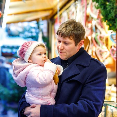 Middle aged father holding baby daughter near sweet stand with gingerbread and nuts. Happy family on Christmas market in Germany. Cute girl eating cookie called Lebkuchen. Celebration xmas holiday.