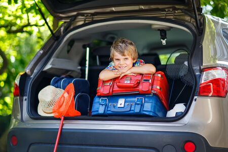 Little kid boy sitting in car trunk just before leaving for vacation
