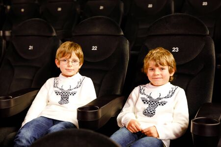 Two little adorable blonde kid boys waiting for a film at cinema. Siblings, twins and brothers having fun with activity of watching movies. Best friends on seats in dark room. Reklamní fotografie - 137690995