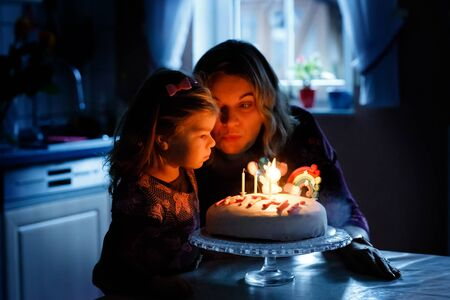 Adorable little toddler girl celebrating third birthday. Baby child daughter and young mother blowing candles on cake and candles. Happy healthy family portrait, mom love and happiness.