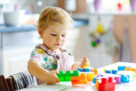 Adorable toddler girl playing with educational toys in nursery. Happy healthy child having fun with colorful different plastic blocks at home. Cute baby learning creating and building. Stock Photo