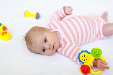 Cute adorable newborn baby playing with lots of colorful rattle toys on white background. New born child, little girl looking surprised at the camera. Family, new life, childhood, beginning concept.