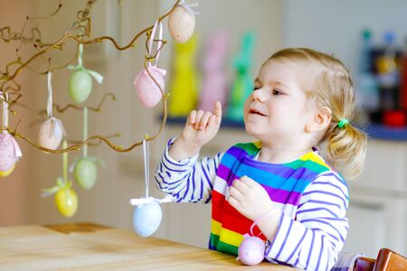 Cute little toddler girl decorating tree bough with colored pastel plastic eggs. Happy baby child having fun with Easter decorations. Adorable healthy smiling kid in enjoying family holiday Stock Photo - 137691099