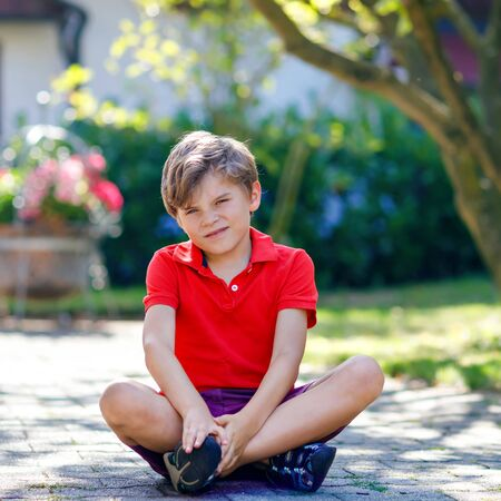Portrait of little cool kid boy sitting on ground on sunny day in domestic backyard. Happy healthy child having fun on warm sunny day. Family, nature, love and active leisure. Kid in school uniform Stockfoto