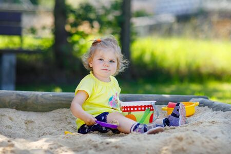 Cute toddler girl playing in sand on outdoor playground. Beautiful baby having fun on sunny warm summer sunny day. Happy healthy child with sand toys and in colorful fashion clothes. Standard-Bild