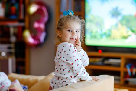 Cute little toddler girl in nightwear pajamas watching cartoons or movie on tv. Happy healthy baby child at home. Zdjęcie Seryjne