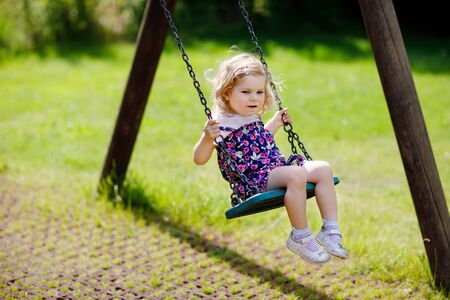 Cute adorable toddler girl swinging on outdoor playground. Happy smiling baby child sitting in chain swing. Active baby on sunny summer day outside