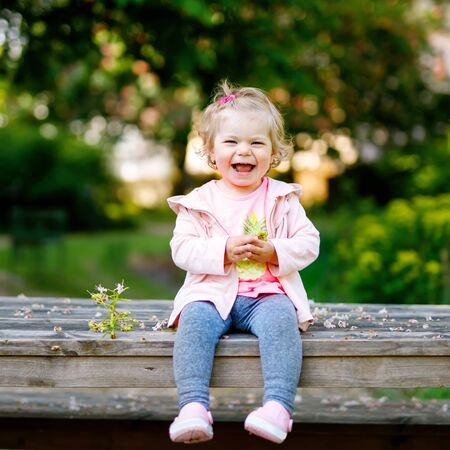 Cute adorable toddler girl playing with blooming chestnut flowers. Little baby child going for a walk on sunny day. Happy healthy kid in colorful clothes Banco de Imagens