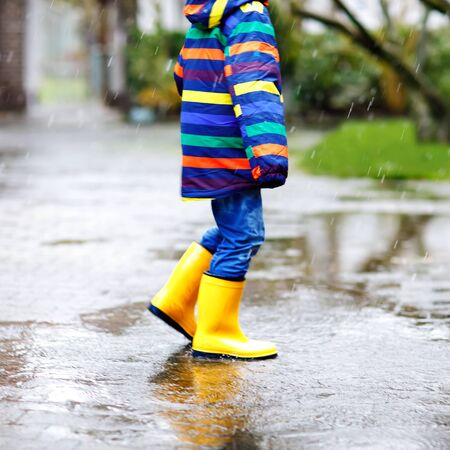 Close-up of kid wearing yellow rain boots and walking during sleet, rain and snow on cold day. Child in colorful fashion casual clothes jumping in a puddle. Having fun outdoors Stock Photo