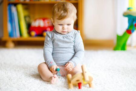 Entzückendes Baby, das mit Lernspielzeug spielt. Glückliches gesundes Kind, das zu Hause Spaß mit buntem verschiedenem Holzspielzeug hat Frühe Entwicklung für Kinder mit Naturspielzeug.