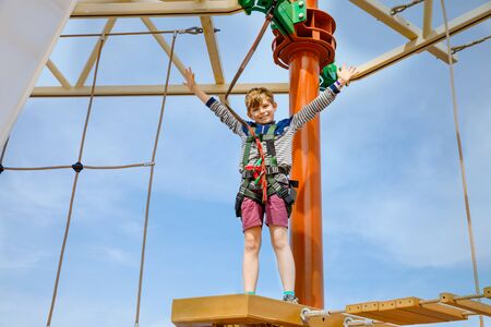 Happy little kid boy climbing on high rope course trail. Active child making adventure and action on family vacations. Challenge for brave kids. Zdjęcie Seryjne