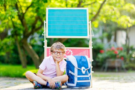 Happy little kid boy with glasses sitting by desk and backpack or satchel. Schoolkid with traditional German school bag called Schultuete on his first day to school. Hello school in German.