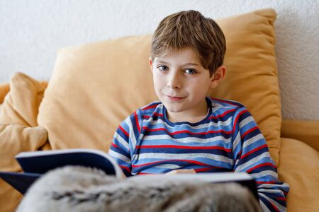 Cute blond little kid boy reading magazine or book in domestic room. Excited child reading loud, sitting on couch. Schoolkid, family, education.