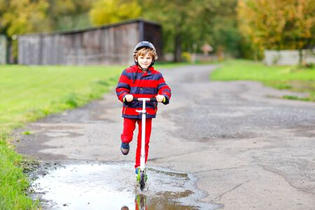 cute little school kid boy riding on push scooter on the way to or from school. Schoolboy of 7 years driving through rain puddle. funny happy child in colorful fashion clothes and with helmet. Stock fotó